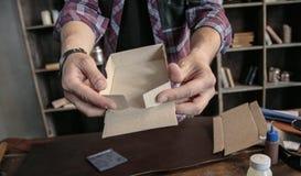 Il creatore del cuoio del giovane monta manualmente il contenitore d'imballaggio di cartone per i prodotti Fotografie Stock