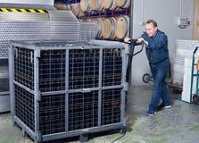 Il creatore del vino scarica i contenitori con le bottiglie Fotografie Stock