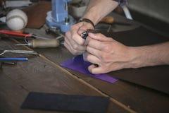 Il creatore di cuoio ha tagliato il cuoio con il coltello pratico sulla tavola di funzionamento di legno Fotografie Stock Libere da Diritti