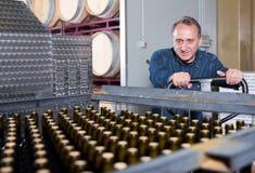 Il creatore felice del vino scarica i contenitori con le bottiglie Fotografia Stock