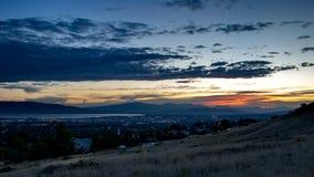 Il crepuscolo cade sopra una città sonnolenta in una valle con le montagne e un lago nei precedenti fotografia stock libera da diritti