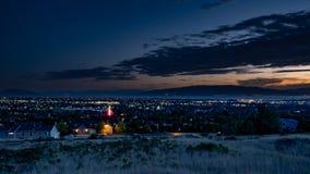 Il crepuscolo cade sopra una città sonnolenta in una valle con le montagne e un lago nei precedenti immagini stock libere da diritti