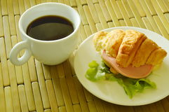 il croissant ha farcito Bologna della carne di maiale e la quercia verde con caffè nero fotografia stock libera da diritti