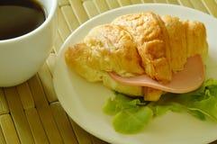 il croissant ha farcito Bologna della carne di maiale e la quercia verde con caffè nero fotografie stock