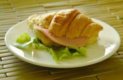 Il croissant ha farcito Bologna della carne di maiale e la quercia verde sul piatto fotografie stock