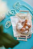 Il croissant si trova su un vassoio e vicino alle perle immagini stock