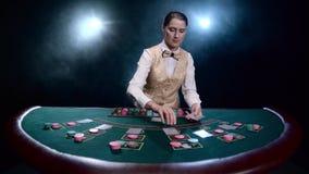 Il croupier della ragazza alla tavola dei chip distribuisce le carte su fondo fumoso nero con i riflettori Movimento lento video d archivio