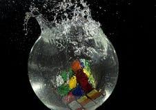 Il cubo di Rubik che cade in un acquario Fotografia Stock