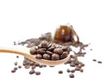 Il cucchiaio dei chicchi di caffè con una tazza di due toni ed il fondo dei fagioli isolati Fotografie Stock Libere da Diritti