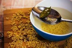 Il cucchiaio di minestra con la pasta dell'alfabeto e la baia vanno Immagini Stock Libere da Diritti