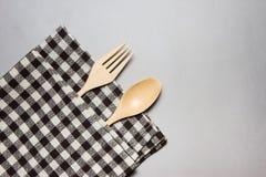 Il cucchiaio e la forchetta di legno con la tavola marrone hanno barrato il tessuto Fotografia Stock Libera da Diritti
