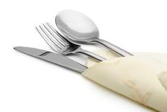 Il cucchiaio, la forchetta e una lama si trovano sul tovagliolo Fotografia Stock