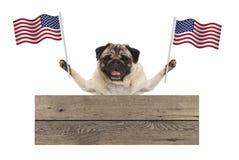 Il cucciolo di cane del carlino con la bandiera nazionale americana di U.S.A. ed il bordo di legno firmano Fotografie Stock Libere da Diritti