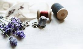 Il cucito degli strumenti con lavander fresco fiorisce su fondo di tela Bobina di legno d'annata, treccia, ditale, bottoni Immagine Stock