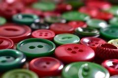 Il cucito verde e rosso si abbottona su una tavola di legno Fotografia Stock