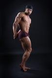 Il culturista bello dimostra il suo corpo potente Fotografia Stock