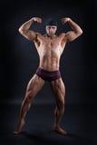 Il culturista bello dimostra il suo corpo potente Fotografia Stock Libera da Diritti
