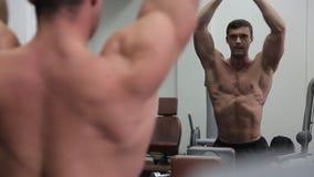 Il culturista davanti allo specchio mostra i suoi muscoli enormi archivi video
