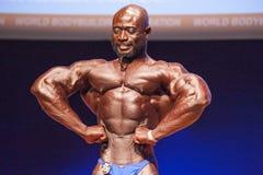 Il culturista maschio flette i suoi muscoli e mostra la sua migliore costituzione fisica Fotografie Stock