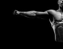 Il culturista muscolare bello che posa e che tiene le armi outstretch Fotografia Stock Libera da Diritti