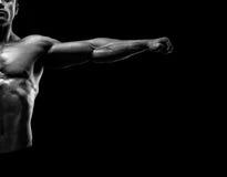 Il culturista muscolare bello che posa e che tiene le armi outstretch Immagine Stock