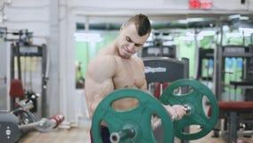 Il culturista muscolare fa l'esercizio per il bicipite nella palestra archivi video