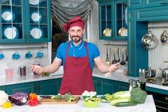 Il cuoco bello invita alla cottura Verdure pronte uomo per la cottura con l'amore Benvenuti del tipo alla cucina Fotografia Stock
