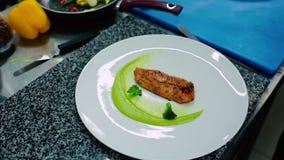 Il cuoco che decora il pesce sul piatto stock footage