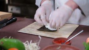 Il cuoco che produce i sushi arriva a fiumi la cucina, spandente il riso sopra il nori video d archivio