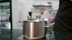Il cuoco dei giovani versa l'acqua e lo zucchero nella casseruola in cucina all'interno video d archivio
