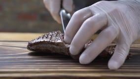 Il cuoco del cuoco unico delle mani che taglia la bistecca della carne sulle fette si chiude su Cucini il taglio della carne arro stock footage