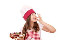 Il cuoco della bambina con il dessert della crostata di ciliege e la mano giusta firmano Fotografie Stock