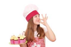 Il cuoco della bambina con i muffin e la mano giusta firmano Immagine Stock
