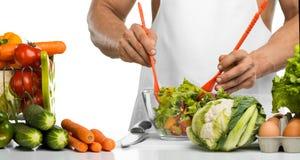 Il cuoco della mano dell'uomo produce a verdure della miscela l'insalata sulla cucina Immagine Stock