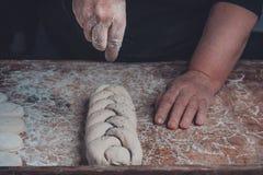 Il cuoco femminile spruzzerà con la pasta del papavero tessuta in una treccia immagini stock