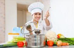 Il cuoco femminile in toque lavora con la siviera Immagini Stock