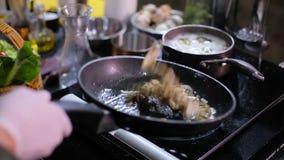 Il cuoco frigge i funghi in una pentola archivi video
