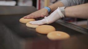 Il cuoco in guanti arrostisce i panini freschi per l'hamburger sulla stufa Alimenti a rapida preparazione Cucina dell'aria aperta stock footage