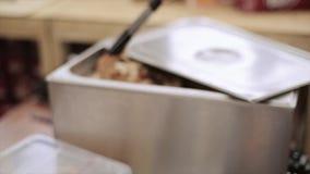 Il cuoco in guanti messi ha preparato i bei pezzi di carne sul panino per l'hamburger Alimenti a rapida preparazione Cucina dell' archivi video