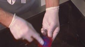 Il cuoco in guanti sfrega le cozze lavate in lavandino con acqua dal coltello, spazzola Cucina del ristorante Pulizia stock footage