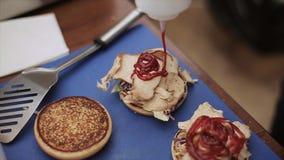 Il cuoco in guanti versa il ketchup sull'hamburger pronto con carne Alimenti a rapida preparazione Panini arrostiti Evento dell'a video d archivio