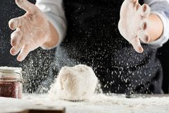Il cuoco impasta la pasta con farina sul tavolo da cucina immagini stock