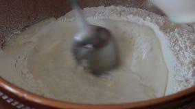 Il cuoco mescola la farina con le uova video d archivio