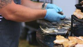 Il cuoco pone il pesce sul barbecue rotondo video d archivio