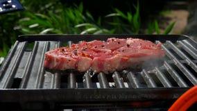 Il cuoco pone una bistecca cruda della carne di maiale con una spatola della cucina