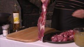 Il cuoco prende un gran pezzo di carne per esaminare video d archivio
