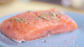 Il cuoco prepara di color salmone sulla griglia stock footage
