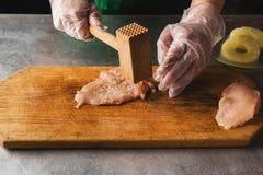 Il cuoco prepara il pollo su un tagliere di legno, mani, pollo, ananas, guanti Inteneritore della carne ricetta per il pollo immagine stock