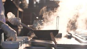 Il cuoco produce le tagliatelle in piastra sulla natura Alimento che cucina sul tramonto archivi video