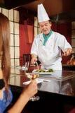 Il cuoco serve il piatto ad un cliente Fotografia Stock Libera da Diritti